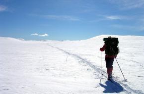 Een toerskiër begint aan de beklimming van een piste